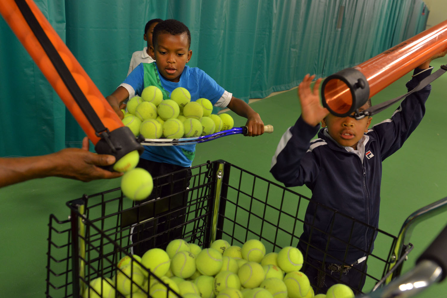 Tayon Richardson and Dexter Humphrey gather tennis balls between drills at the Washington Tennis & Education Foundation's new $10 million Southeast DC tennis and learning center on Thursday, June 6, 2013, in Washington, DC.