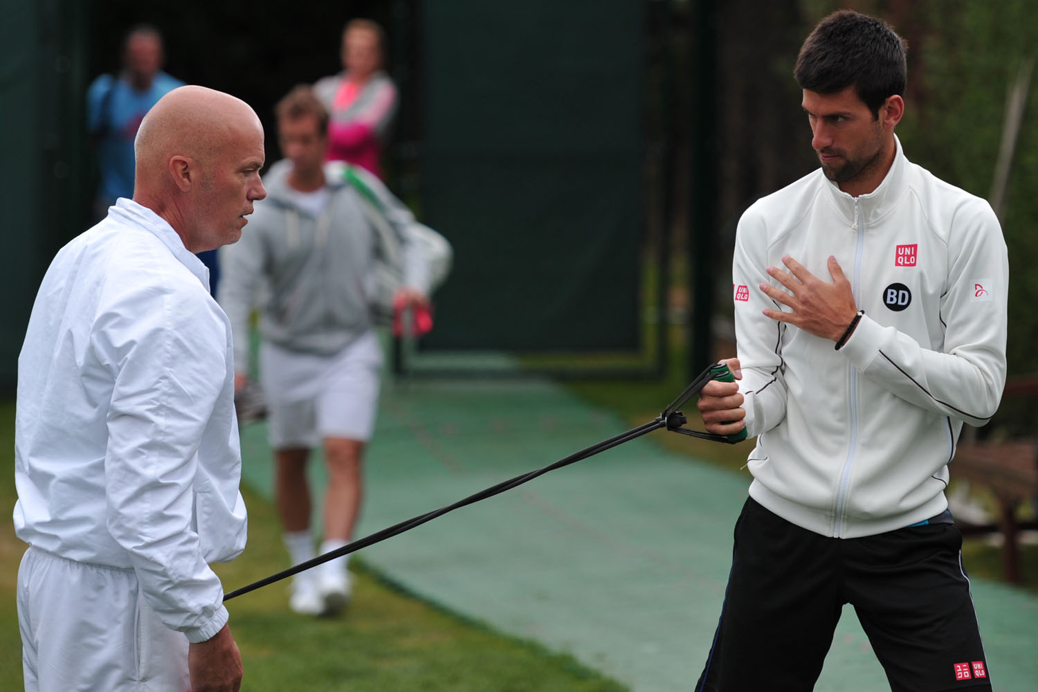 Novak Djokovic works out with a resistance band during a training session at the All England Tennis Club in Wimbledon, southwest London, on June 23, 2013, on the eve of the start of the 2013 Wimbledon Championships.
