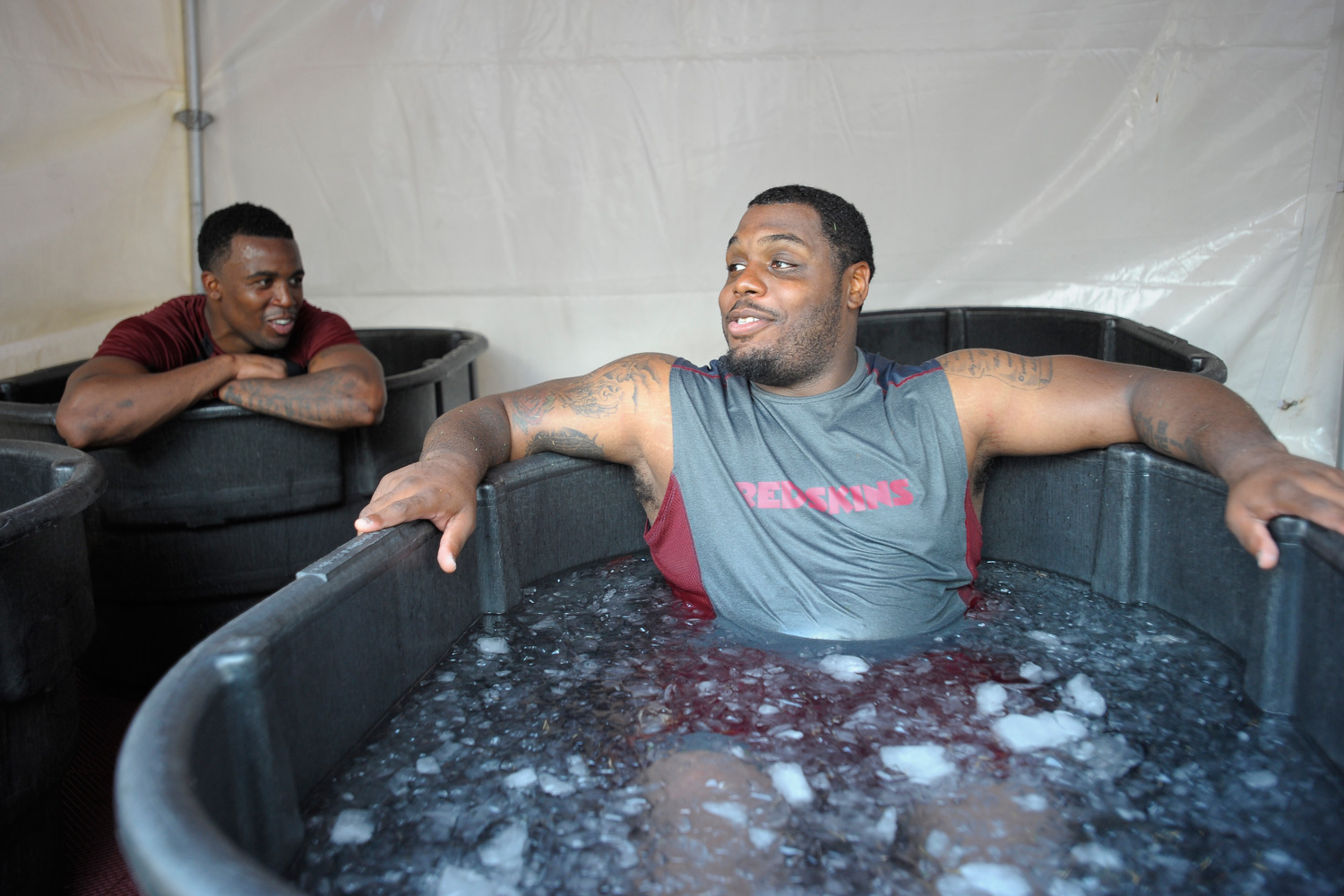 Former Washington Redskins wide receiver Darius Hanks (L) talks with former defensive lineman Chris Baker (R) as they cool off following the first day of training camp in July 2012.