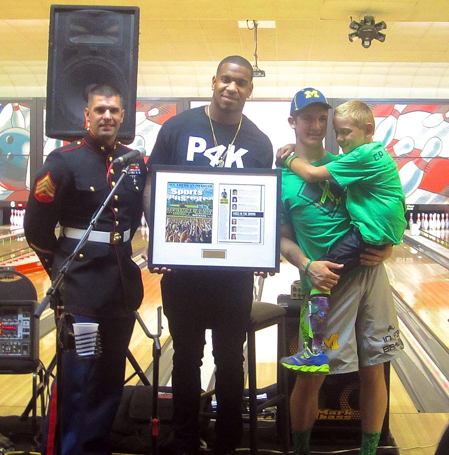 Sgt. Scott Comment and Eric Ebron present Hunter (with Braden close at hand) with a framed commemorative copy of his issue of Sports Illustrated.