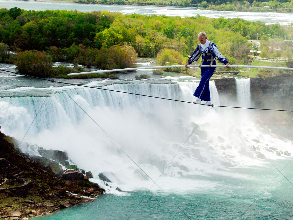 Canadian Jay Cochrane perilously walks on a high wire approximately 40 stories above the American Falls at Niagara Falls. Cochrane's walk covered a distance of 200 feet - from the pinnacle of the Sheraton on the Falls Hotel to the Casino Tower.