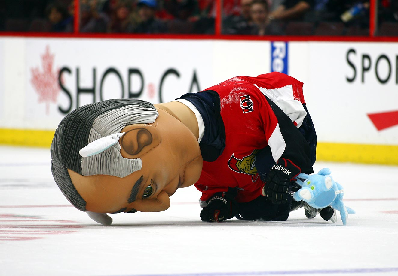Sir John McDonald falls while trying to collect eggs in his easter basket during the Prime Ministers race at the game between the Capitals and Senators.