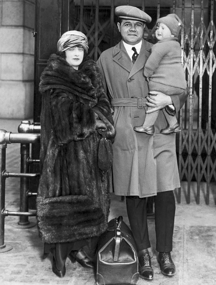 Babe Ruth poses at Pennsylvania Station with his then-wife Helen Ruth and daughter Dorothy as he prepares to leave for Yankees spring training camp in 1923.
