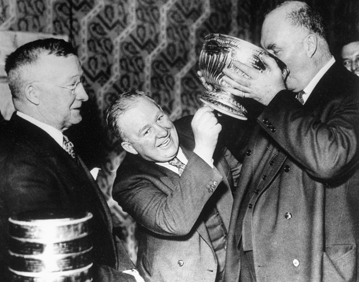 Their names have become synonymous with hockey excellence: NHL president Frank Calder (left) watched as Detroit coach Jack Adams and owner James Norris drank from the Cup to celebrate the first championship in franchise history. The Red Wings won their best-of-five final against Toronto, three games to one.