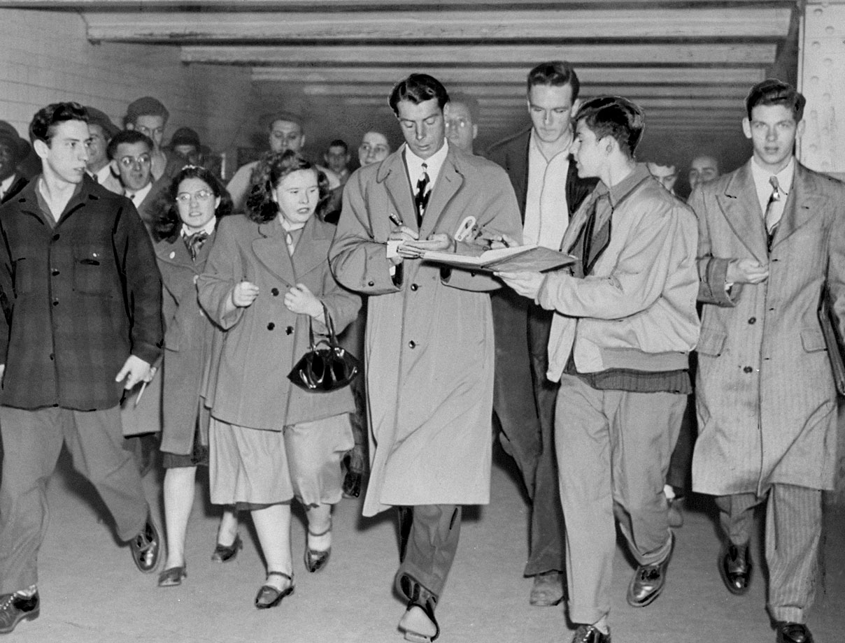 Joe DiMaggio signs autographs for fans who met him at Pennsylvania Station when he arrived back in town with the New York Yankees on April 16, 1948.