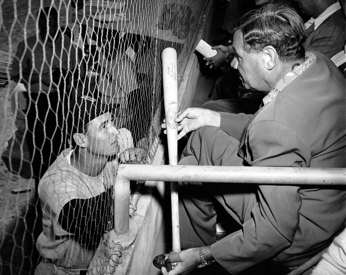 Ted Williams receives some hitting advice from Babe Ruth during a spring training game in 1948.