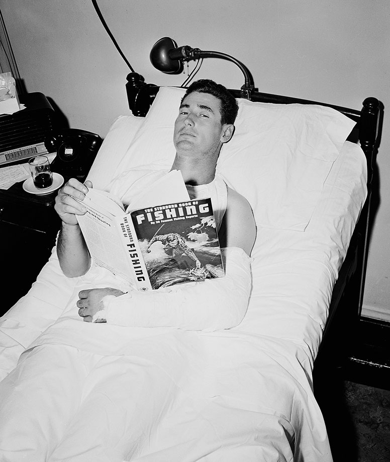 Post-surgery, Ted Williams relaxes in his hospital bed. He had bone fragments removed from his left elbow after crashing into a wall to make a catch in the 1950 All-Star game.