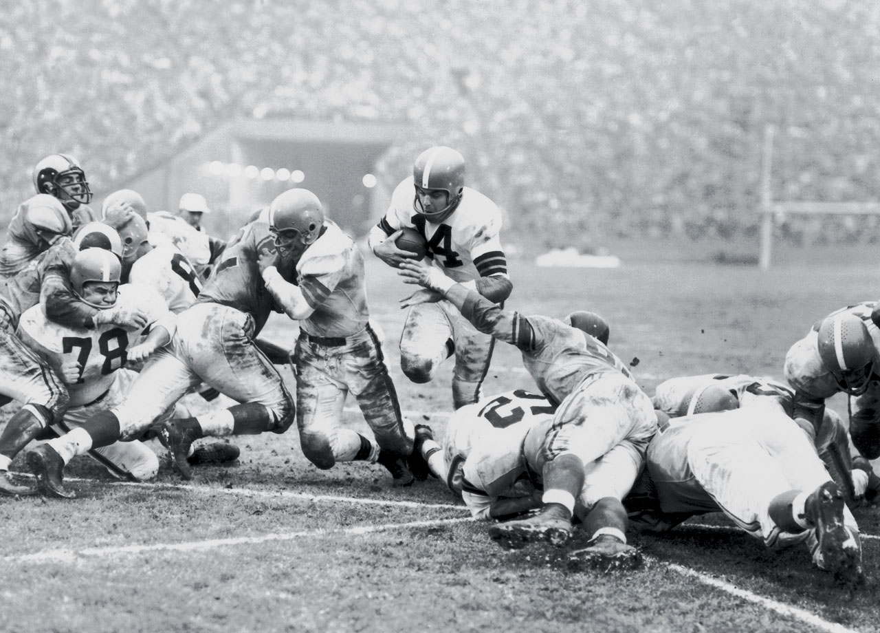 Graham nearly retired after leading the Browns to the '54 NFL title, but returned for a final hurrah -- and a then-NFL record salary of $25,000. In 1955 he led the league in passing, completion percentage and yards per attempt as the Browns won another Eastern Conference title with a 9-2-1 record.  In the '55 NFL title game against the Los Angeles Rams, Graham, 34, passed for two touchdowns and ran for two more as the Browns coasted to a 38-14 victory. Late in the game, when Graham left the field for the last time, the L.A. Coliseum crowd gave him a standing ovation.