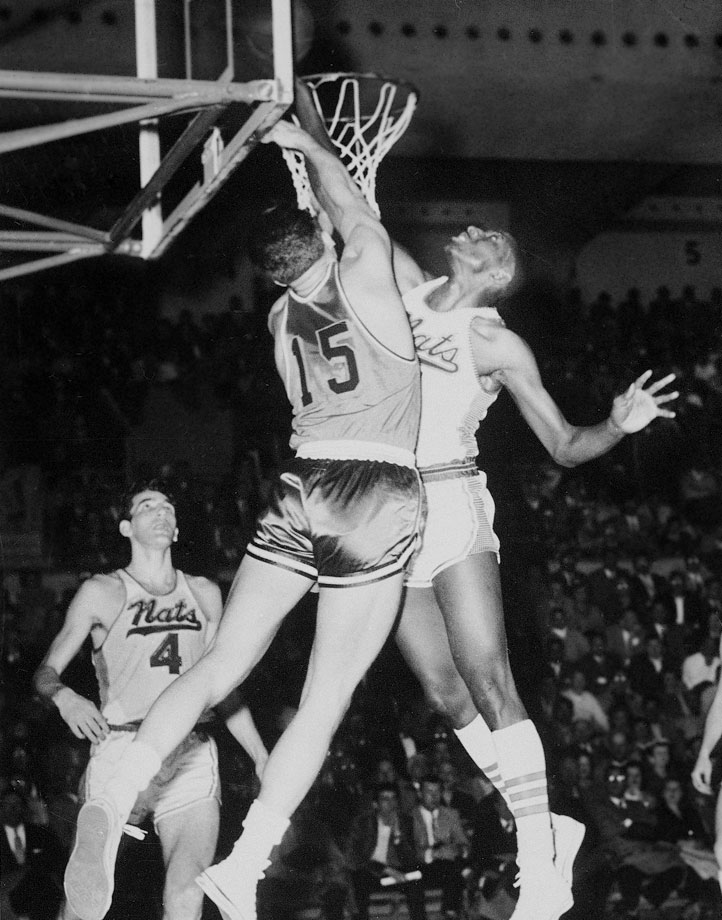 Earl Lloyd shoots a layup against Tom Gola during a game between the Syracuse Nationals and Philadelphia Warriors in 1956.