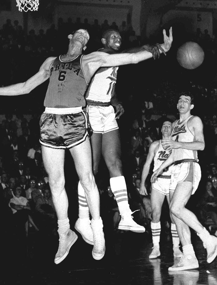 Earl Lloyd blocks a shot by Neil Johnson during a game between the Syracuse Nationals and Philadelphia Warriors in 1956.