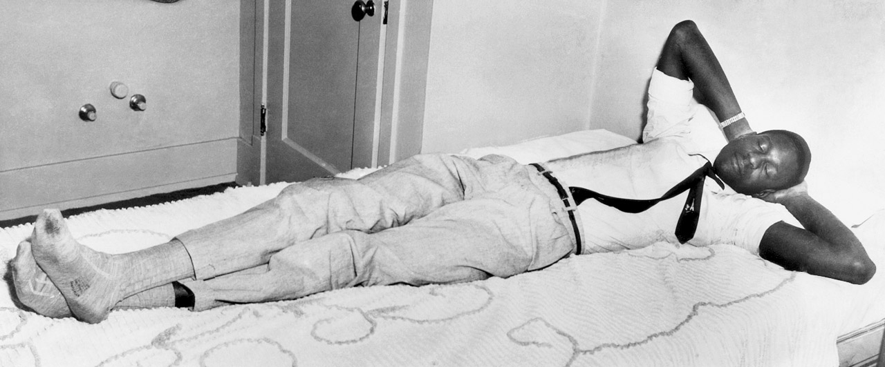 Bill Russell takes a snooze before the NCAA regional basketball playoffs in Corvallis, Ore. His 6-10 frame leaves little to spare on the 7-foot bed.
