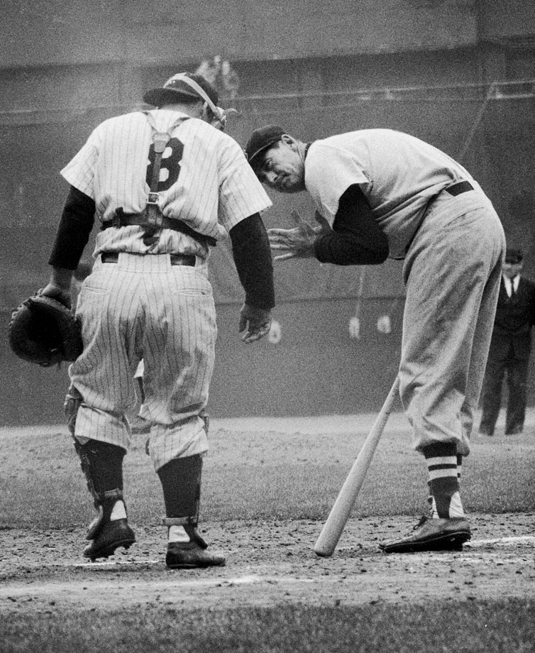 Ted Williams looks back at Yankees catcher Yogi Berra during an at-bat in 1956.