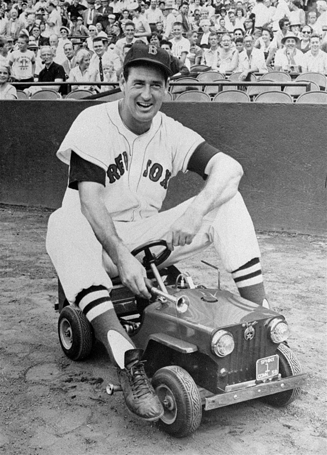 Ted Williams sits atop a miniature car before a game in 1958.