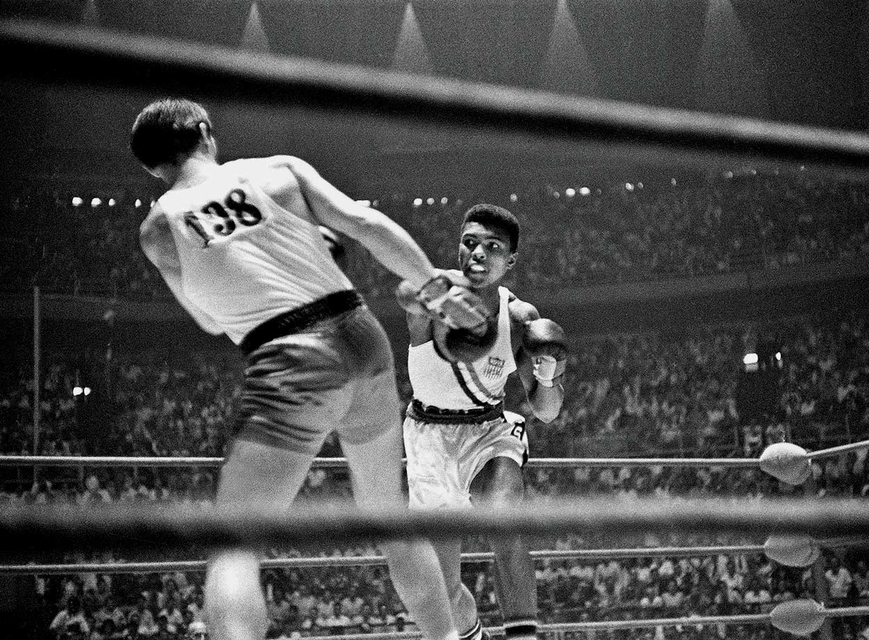 Cassius Clay punches Zbigniew Pietrzykowski of Poland during their gold medal bout at the 1960 Rome Olympics. Clay defeated Pietrzykowski 5-0 for the light heavyweight gold medal.