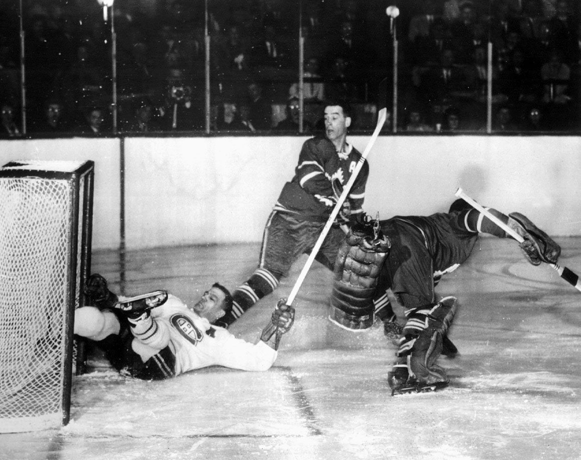 "Toronto goalie Johnny Bower barely avoided being bowled over by Bernie ""Boom Boom"" Geoffrion during the first period in Game 4, but there was no stopping Montreal's steamrolling Habs. Making their 10th straight appearance in the final, the Canadiens captured their record fifth consecutive Cup by sweeping the Leafs. The series finale marked the final NHL game of the great Rocket Richard."