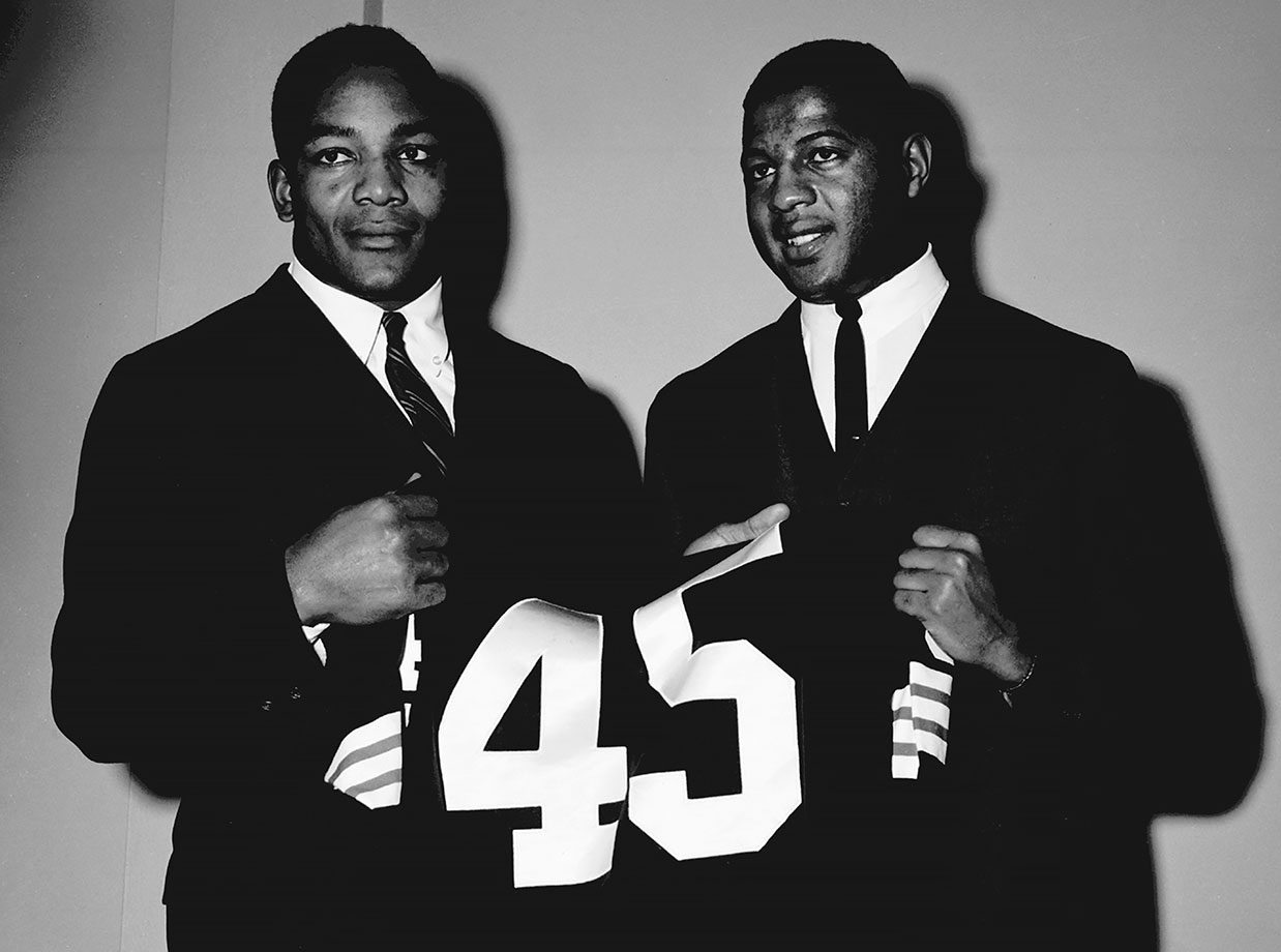 Jim Brown and Ernie Davis hold up Davis' No. 45 Browns jersey. Brown and Davis were set to be teammates with the Cleveland Browns, but Davis was diagnosed with leukemia while preparing for the 1962 College All-Star Game and died in 1963. The Browns retired Davis' jersey after his death.