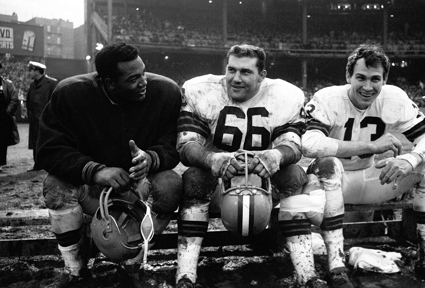 Jim Brown chats with teammates Gene Hickerson and Frank Ryan on the Cleveland Browns bench during a game in 1964 against the New York Giants at Yankee Stadium, the Giants' home stadium from 1956 to 1973.