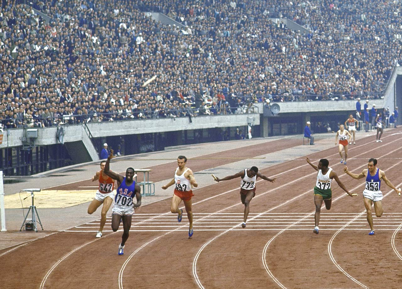 "One of history's greatest sprinters, Hayes erupted at the 1964 Tokyo Olympics. Despite running the 100-meter final on a cinder track's inside lane, a lane that had been chewed up by the start of the 20-kilometer walk, Hayes pulled away to win by seven feet, a margin Track and Field News described as ""almost insulting to an Olympic field."" The 4x100-meter relay final was the stuff of legend. Anchoring what amounted to a U.S. ""B"" team, Hayes received the baton nearly three meters behind the leaders. His acceleration seemed to defy the laws of nature. Within 30 meters Hayes was in front and he finished more than 2 meters ahead in a world record 39.06. His 100 leg was unofficially timed in 8.6."