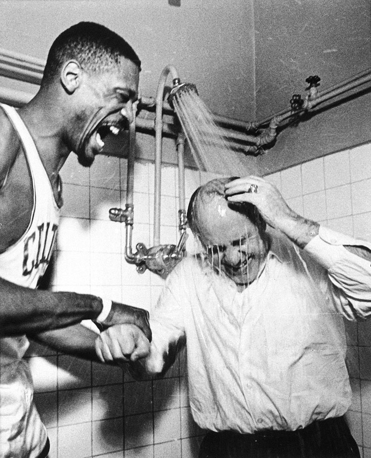 "Bill Russell ""persuades"" Celtics coach Red Auerbach to take a shower with his clothes on Boston won their seventh consecutive NBA championship."