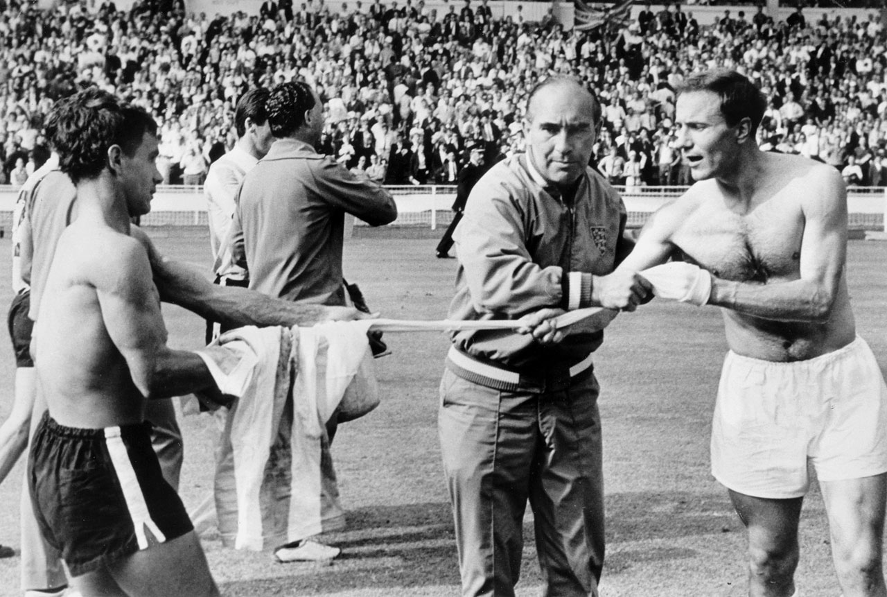 English manager Alf Ramsey does his best to stop defender George Cohen from swapping shirts with Argentina's Alberto Gonzalez following a stormy, ill-tempered match in a quarterfinal of the 1966 World Cup.