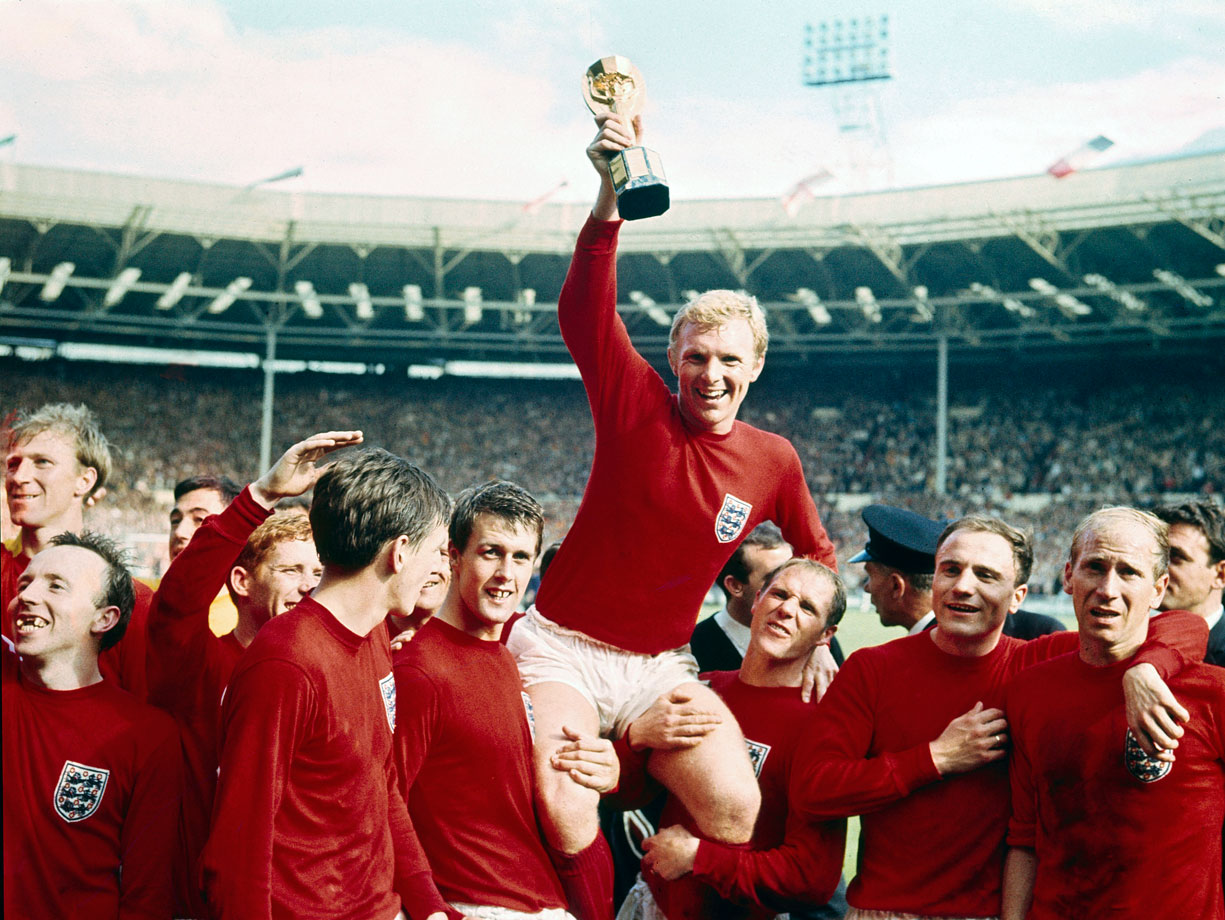 English captain Bobby Moore soaks in the adulation of the home fans as his teammates hoist him and the World Cup trophy on their shoulders following the conclusion of the final.