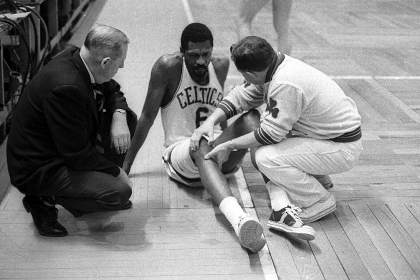 A trainer checks on the injured center during a game.