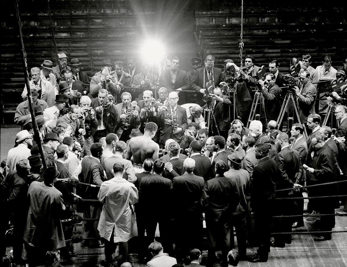 Leifer, thinking outside the box and outside the ring captured the crowd of cameras surrounding Ali, as the champion weighed in for his fight against Zora Folley at Madison Square Garden in March 1967.