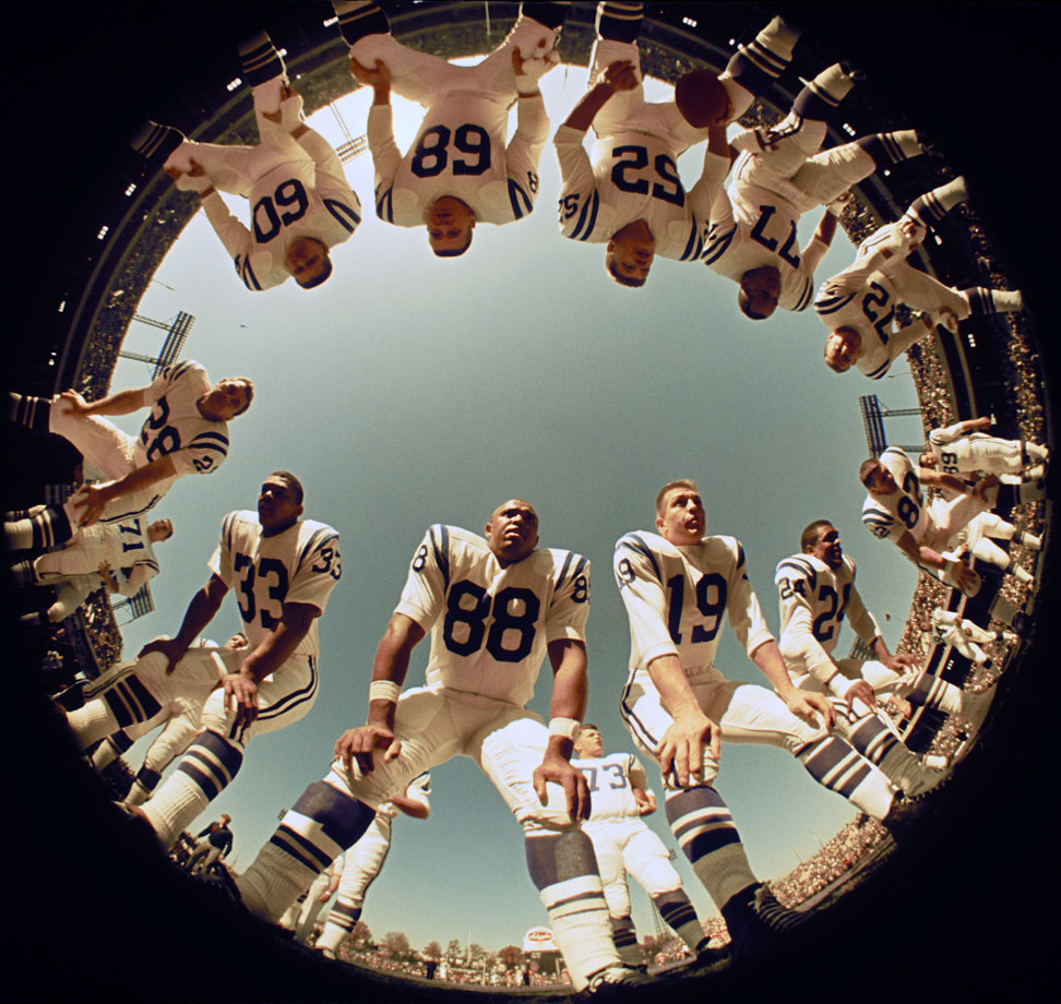 John Mackey (88) and Johnny Unitas (19) huddle with their fellow Colts during practice at Memorial Stadium, shot with a fisheye lense.