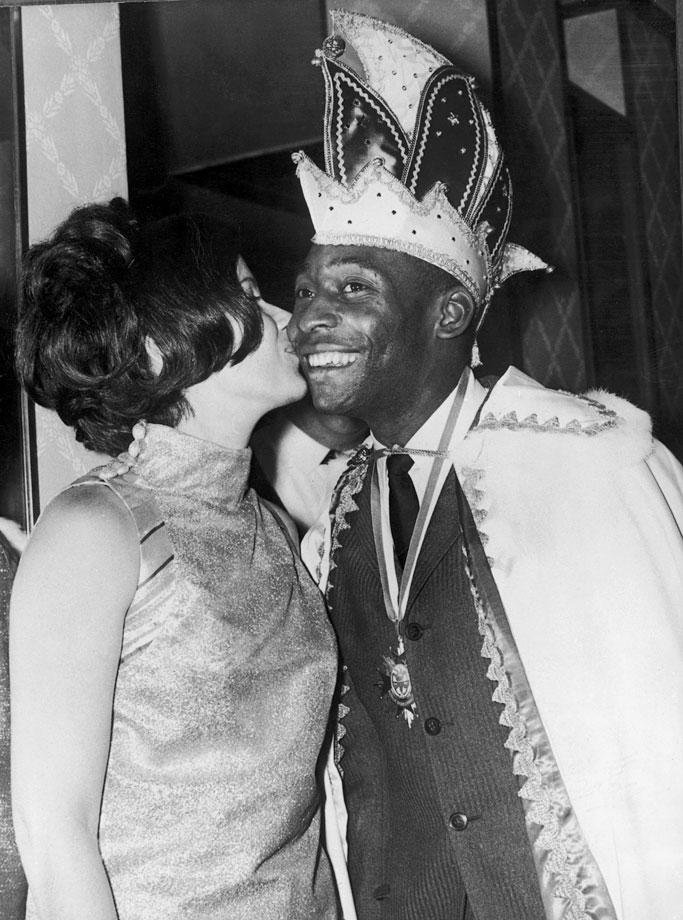 Pelé receives a kiss from his wife at a sportsman's ball in Munich, February 1968. He is wearing a cloak and a headdress in his role as King Carnival.