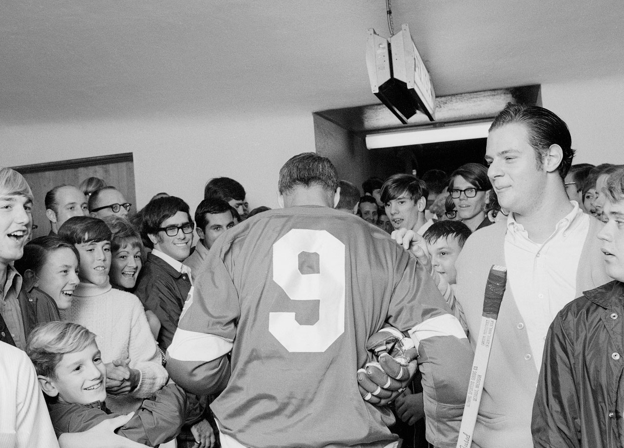 Gordie Howe is surrounded by fans as he walks from the locker room to the ice for the Detroit Red Wings season opening game against the Toronto Maple Leafs at Olympia Stadium in Detroit. Howe spent 25 seasons with the Red Wings and still holds eight franchise records, including games played (1,687), goals (786) and points (1,809).