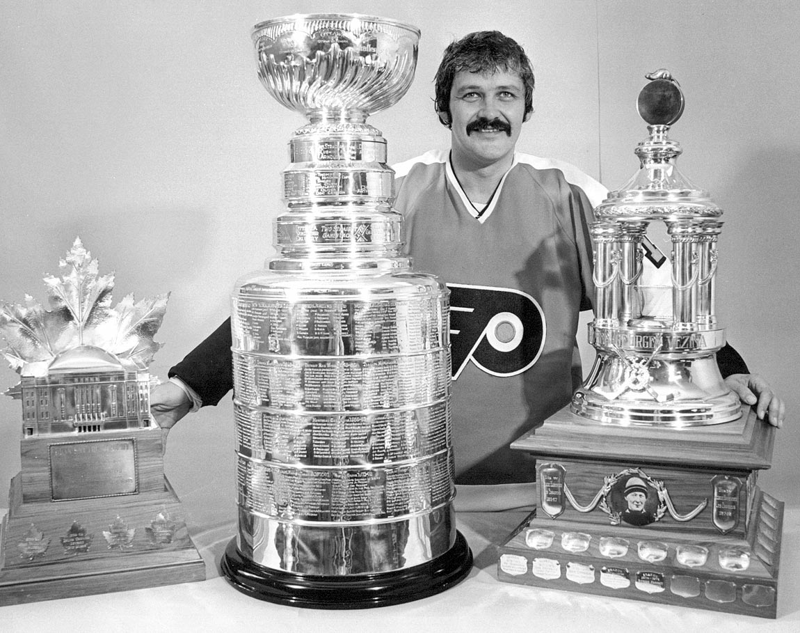 Bernie Parent poses with the Stanley Cup, Conn Smythe and Vezina trophies after having won them all for a second consecutive time in 1975.