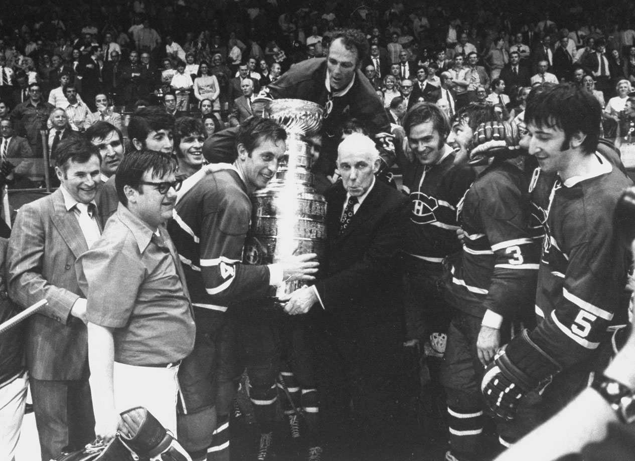 After the Canadiens defeated the Chicago Blackhawks in Game 7, the career of their legendary captain Jean Beliveau came to an end as he was presented the Stanley Cup by NHL president Clarence Campbell while teammates (left to right) Henri Richard, Ken Dryden, Jean-Claude Tremblay and Guy Lapointe looked on.