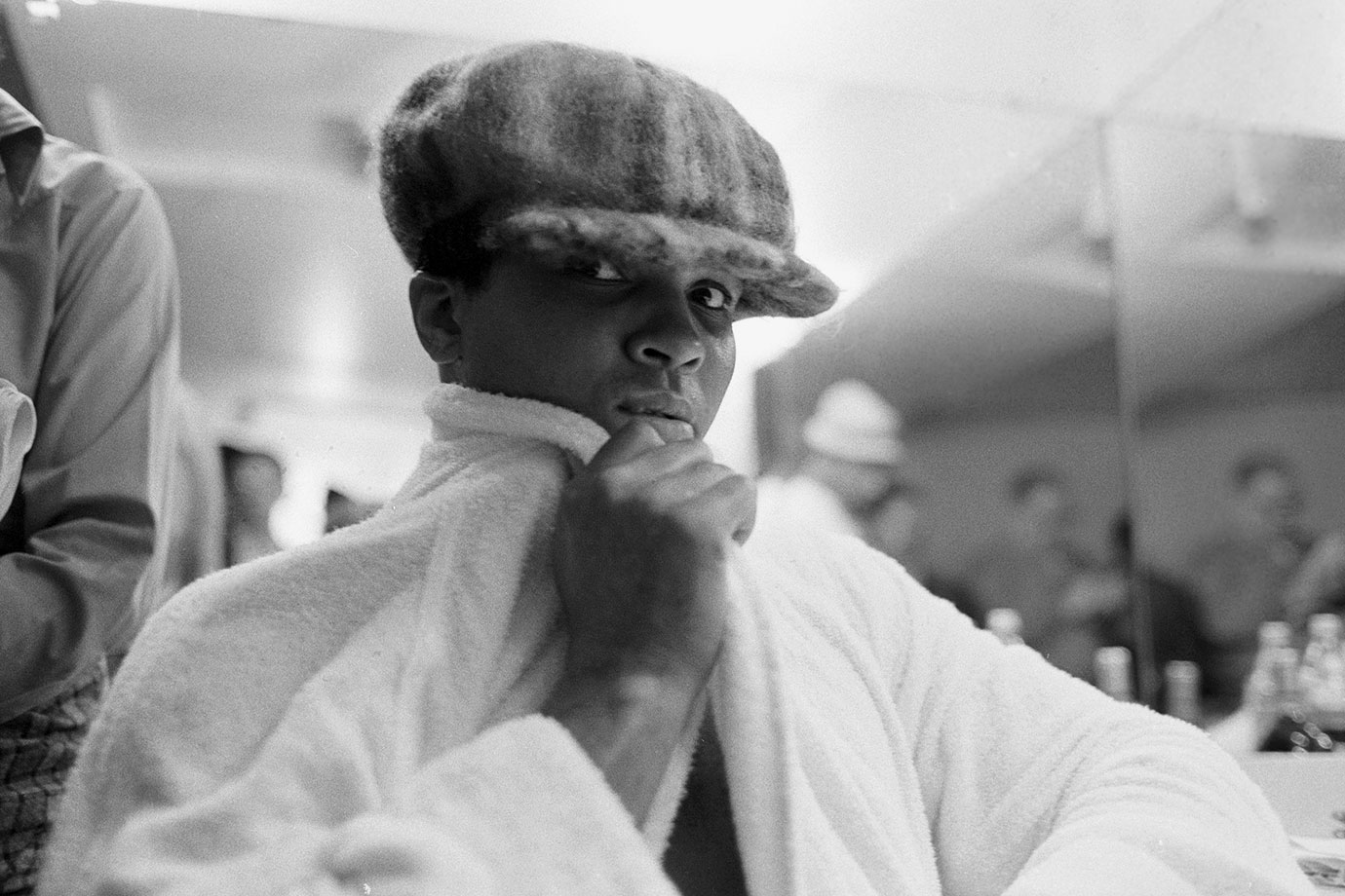 In a lighter pre-fight moment, Ali poses for a portrait wearing a hat in his dressing room before the match with Bugner.
