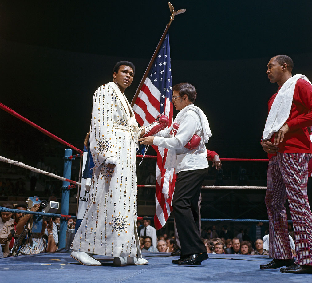 Muhammad Ali, wearing a robe given to him by Elvis Presley, has his glove laces tied by trainer Angelo Dundee before his fight with Joe Bugner in Las Vegas on Feb. 14, 1973.