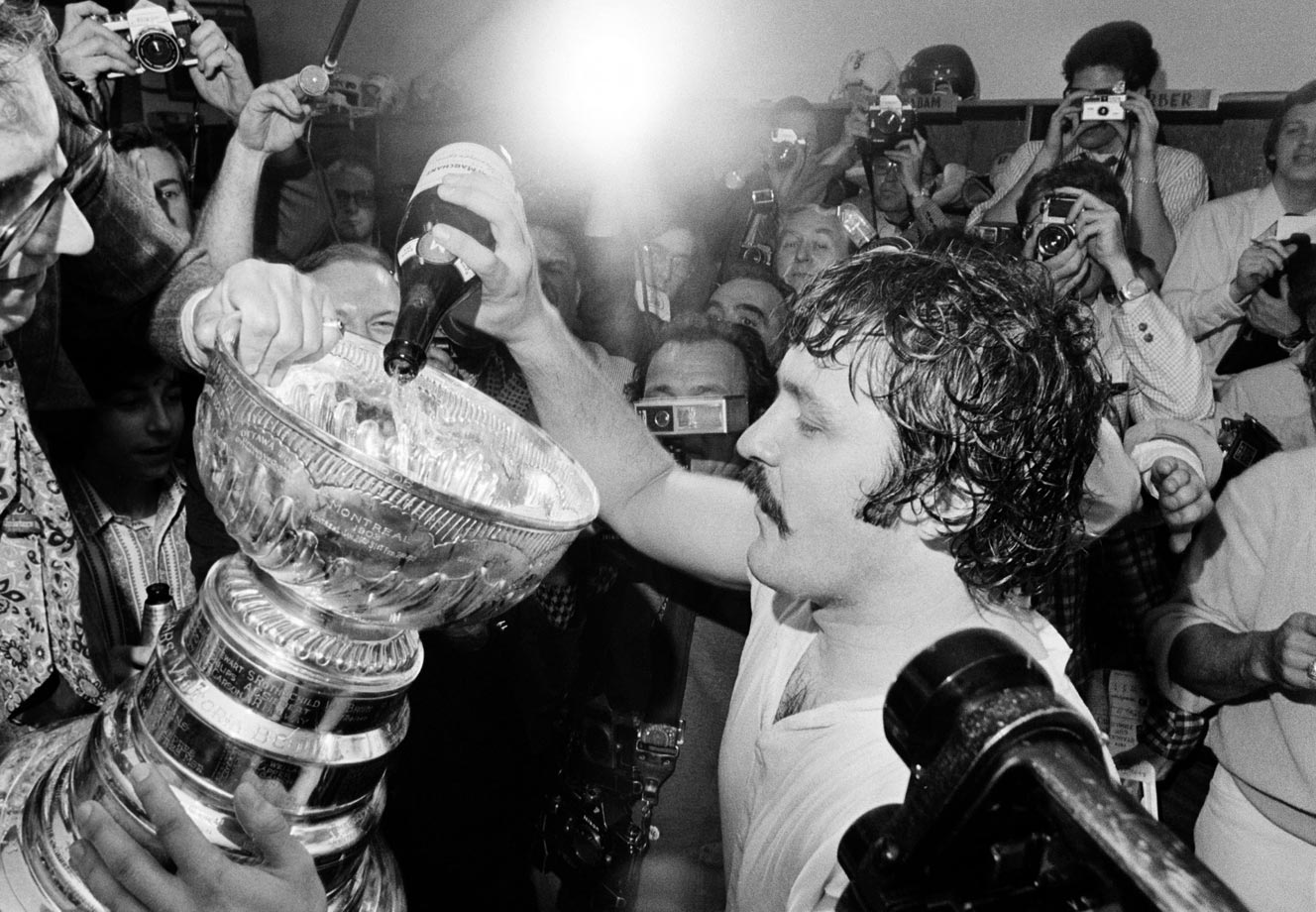 Bernie Parent pours champagne into the Stanley Cup following Game 6 on May 19, 1974 in Philadelphia. Parent posted an epic 30-save shutout against the Bruins as the Flyers won the game 1-0 and the series four games to two.