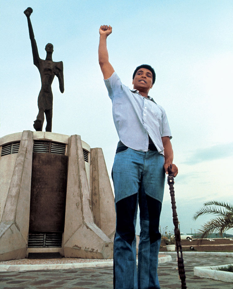 Ali poses in front of the Le Militant statue at the presidential complex that was the site of Ali's January heavyweight title bout with Foreman. The fight was originally set for a month earlier, but Foreman suffered a cut near his eye during training, forcing a delay.