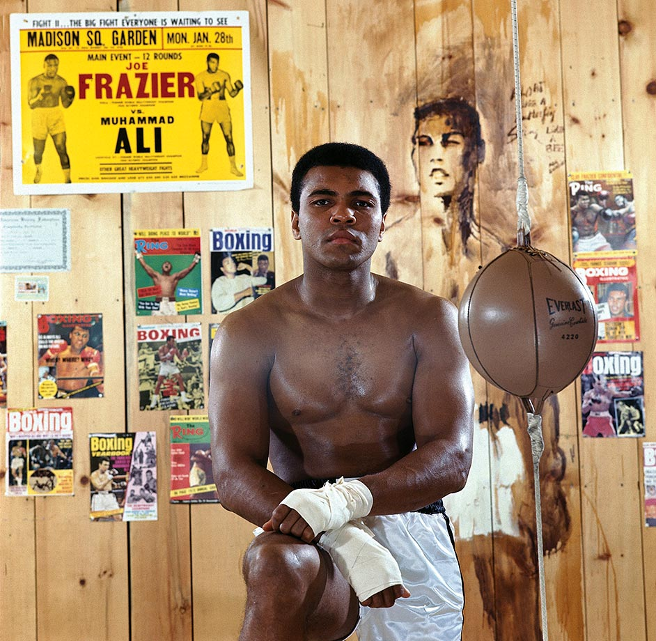 Ali poses in front of posters and magazine covers from throughout his career at his training camp cabin in Deer Lake in 1974.