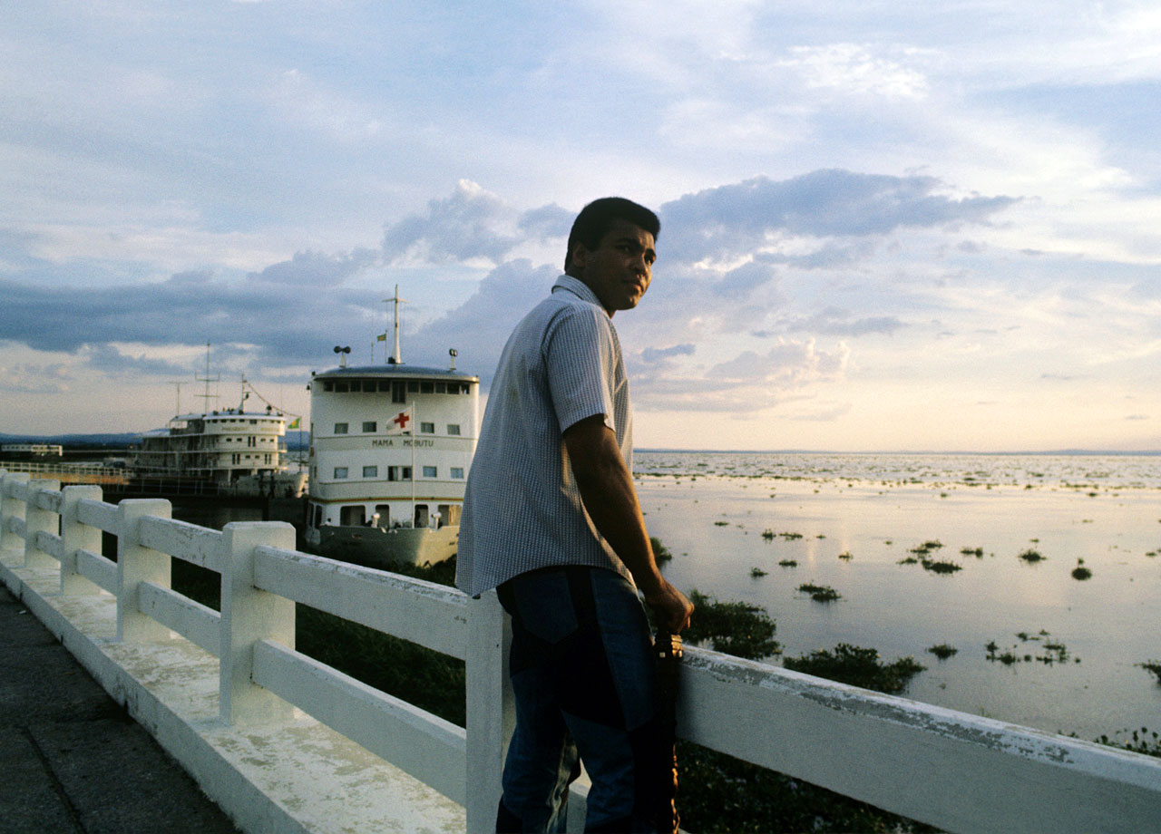 Ali stands against the railing on the River Zaire watching the sunset four days before the Rumble in the Jungle. The fight was sponsored by Zaire to achieve the $5 million purse promoter Don King had promised both Ali and Foreman.