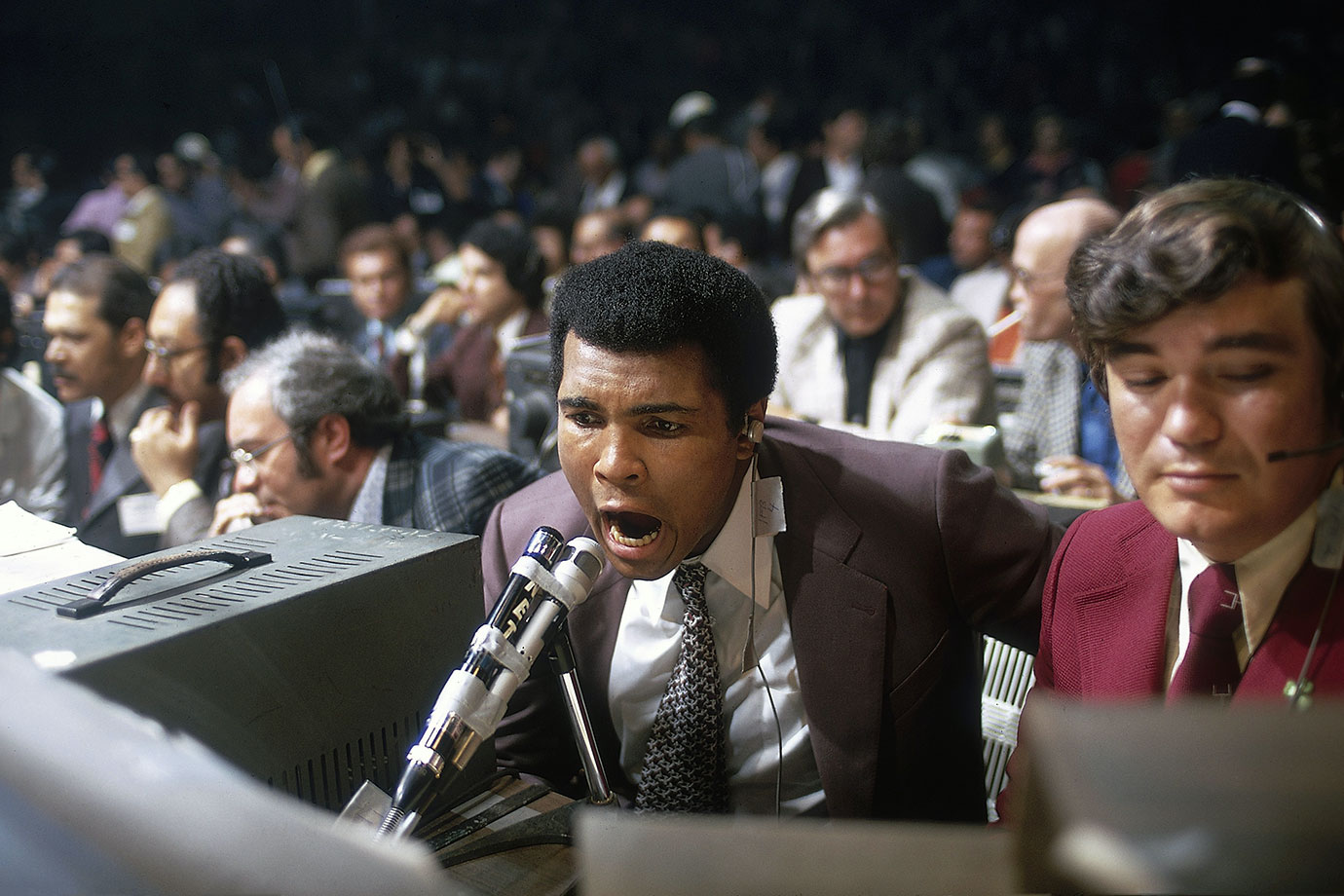 Exploring a different side of the sport, Ali broadcasts the fight between George Foreman and Ken Norton in March 1974. Foreman won the fight by technical knockout in the second round, setting up the showdown with Ali in Zaire.