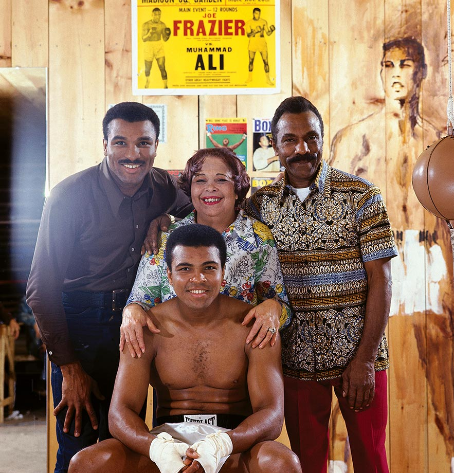 Ali poses with members of his family in front of a poster from his first fight with Joe Frazier. Ali's brother, Rahman Ali; mother, Odessa Clay; and father, Cassius Clay Sr. stand behind the boxer.
