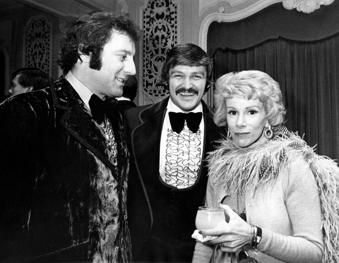 Blackhawks goalie Tony Esposito and Flyers goalie Bernie Parent chat with comedienne Joan Rivers during the 27th annual NHL All-Star Game dinner on Jan. 28, 1974 in Chicago.