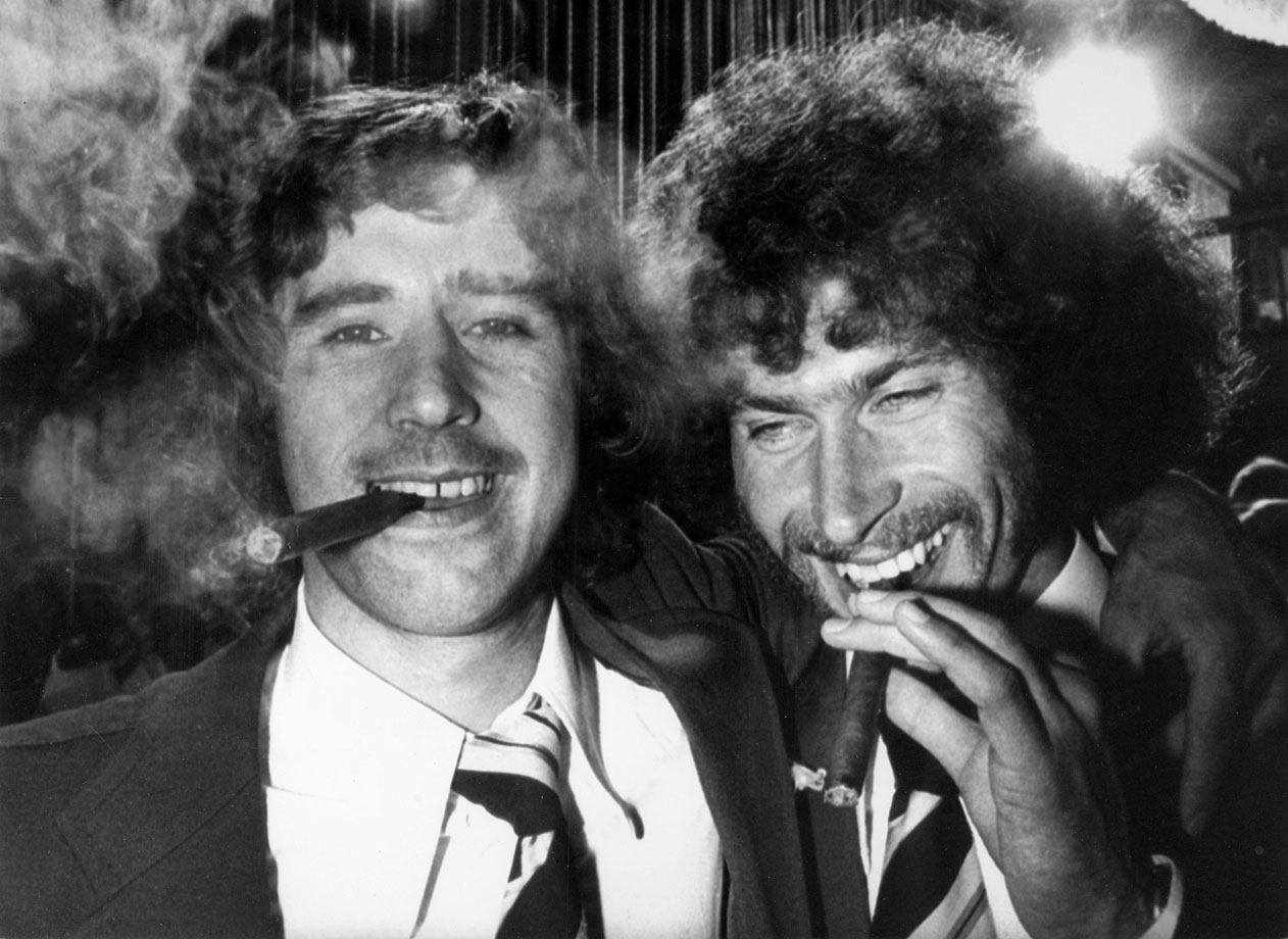 West Germany's Gerd Müller and Paul Breitner, the two West German goal scorers in the 1974 World Cup final, celebrate at the after-match banquet by smoking cigars.
