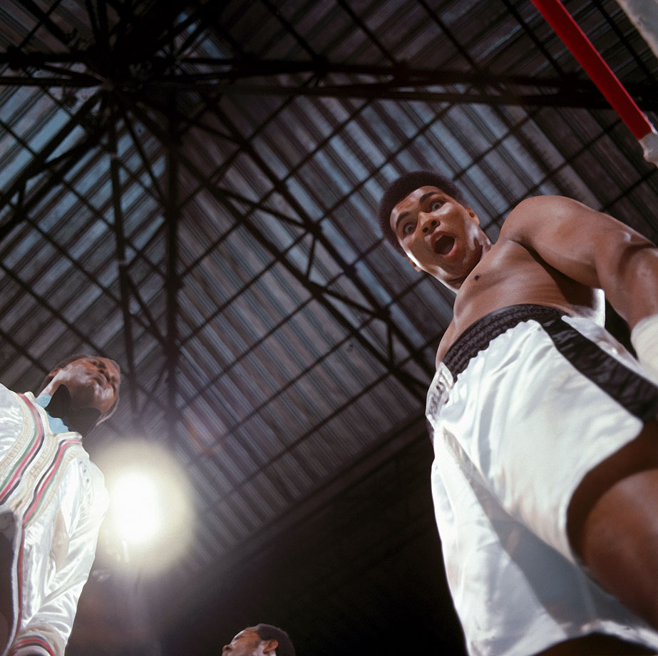 "Muhammad Ali makes a face at the camera before the fight.  After refusing to enter the draft in 1967, Ali was suspended from boxing for more than three years.  When he returned to the ring in 1970, he claimed two victories before falling short against titleholder Joe Frazier in the ""Fight of the Century"" in 1971.  The bout with Foreman was Ali's chance to regain the WBA and WBC belts."