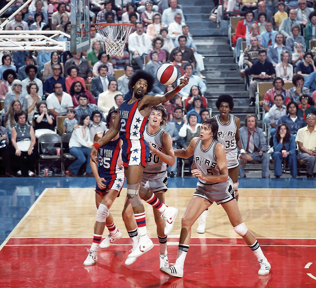 Dr. J pulls down a rebound as San Antonio's Allan Bristow (30), Bill Paultz (5) and Larry Kenon (35) look on.