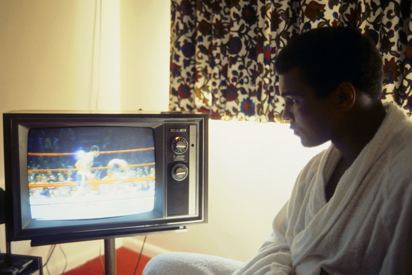 Before his 1976 fight against Ken Norton at Yankee Stadium, Ali watches a fight on television from his hotel room. A police strike at the time of the fight created a dangerous environment outside the stadium that all but eliminated walk-up sales.