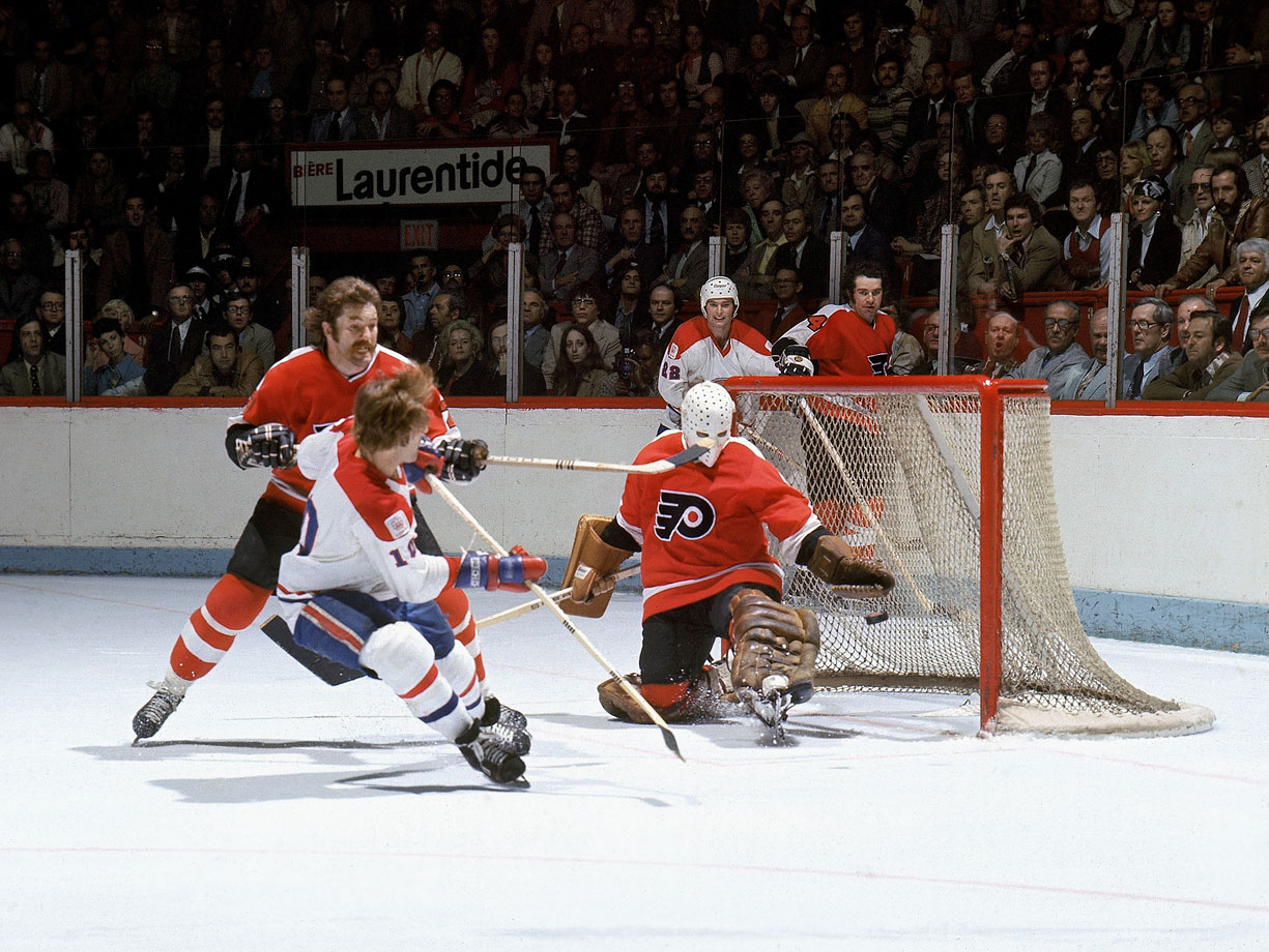 Despite heavy checking from Philadelphia's Dave Schultz, Montreal's flashy Guy Lafleur managed this shot on net against Flyers goalie Wayne Stephenson in Game 2 at the Montreal Forum. The Canadiens won, 2-1, and went on to a sweep as Lafleur scored the clincher in Game 4.