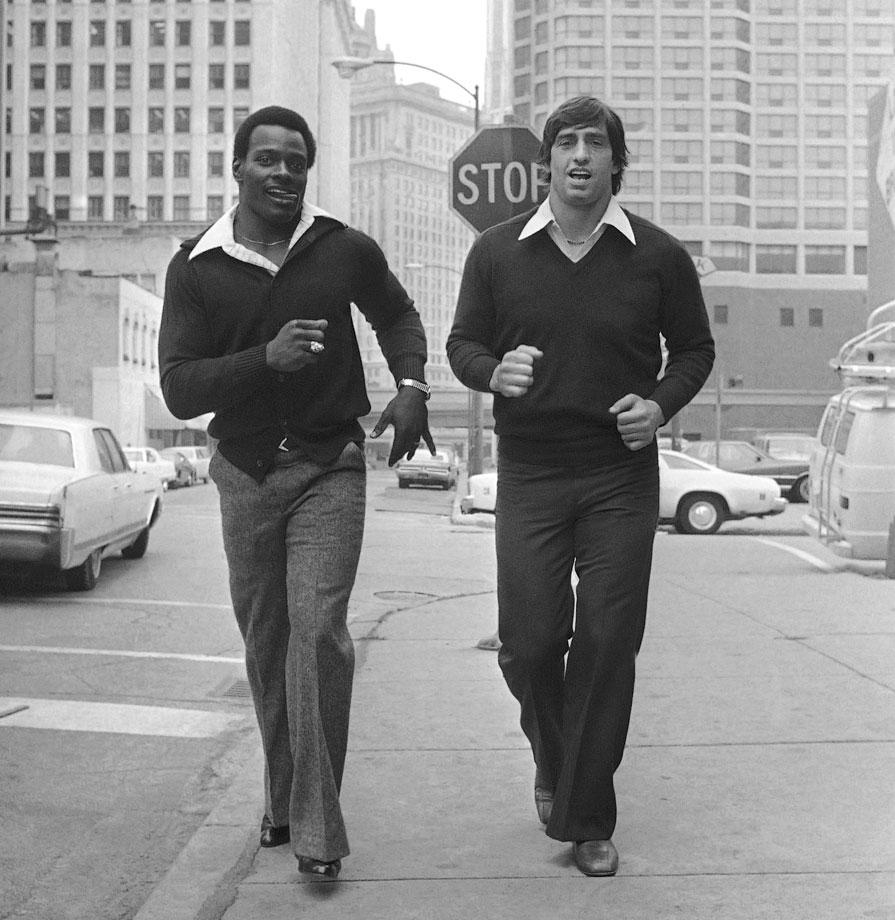 Walter Payton jogs down the street in Chicago with his teammate, Bears linebacker Doug Buffone, following a press conference on Oct. 31, 1977.
