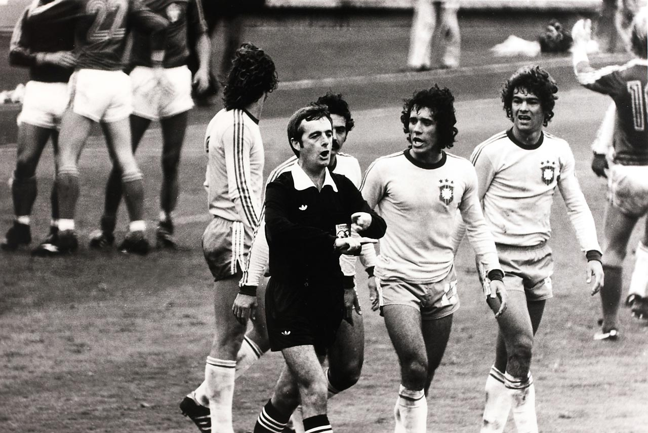 Angry Brazilian players follow Welsh referee Clive Thomas after the conclusion of Brazil's second-round match with Sweden.  Thomas blew his whistle for full time while Brazilian Zico scored a free kick, inexplicably discounting the goal and ending the game.