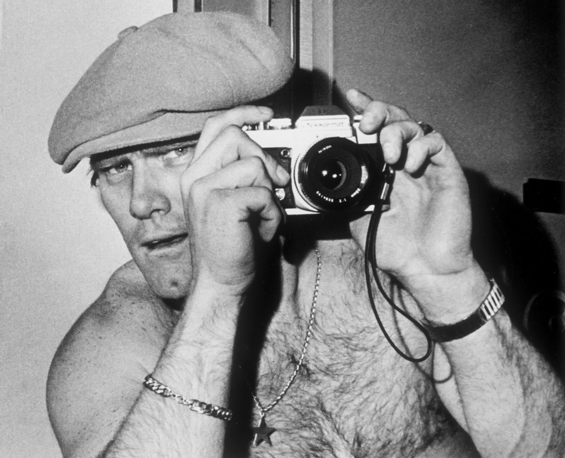 A candid Terry Bradshaw poses for the camera, with a camera.