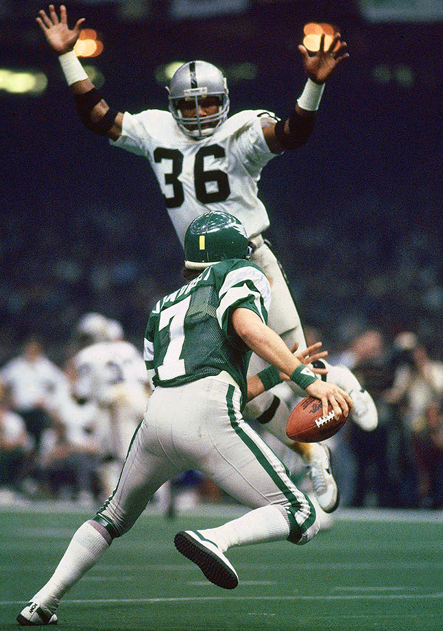 Philadelphia Eagles quarterback Ron Jaworski scrambles away from Oakland Raiders defensive back Mike Davis. Oakland defeated Philadelphia 27-10 as Jaworski completed less than half of his pass attempts with three interceptions.